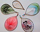 6 gotas indigenas - 1 metal banhada em prata  com detalhes floridos e 5 em linhas coloridas